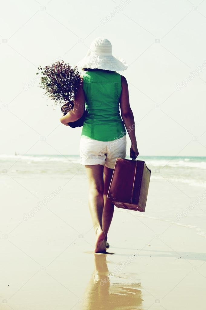 Young woman with a tree and a vintage suitcase walking on the edge of the sea  Stock Photo #14918241