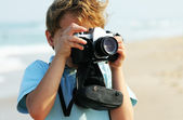 Cute 7 years old boy with old camera — Stock Photo