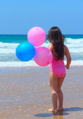 Beautiful girl 5 years old on the beach with balloons — Stock Photo