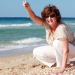 Happy senior woman at the beach - Stock Photo