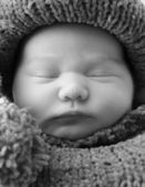 Newborn in a knitted cocoon and hat — Stock Photo