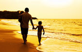 Father and two kids silhouettes on the beach at sunset — Stock Photo