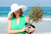 Beautiful girl with tree on the beach — Stock Photo