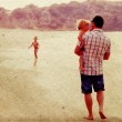Father with two kids on vacation at sea on sunset colours — Stock Photo #21961465