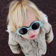Funny 2 years old girl with sunglasses outdoors - Stock Photo