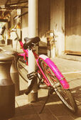 Old pink bicycle. Photo in old image style. — Stock Photo