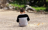 Sad boy sitting alone in nature, autism syndrome — Stock Photo
