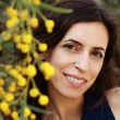 Portrait of smiling woman outdoors with yellow flowers — Stock Photo