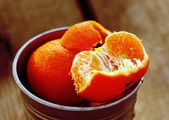 Tangerines in a bucket on a natural wooden table — Stock Photo