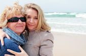 Mother and daughter on a winter beach — Stock Photo