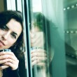 Royalty-Free Stock Photo: Beautiful 35 years old woman next to the window. Photo in old im