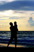 Father and daughter playing together on the beach at sunset — Stock Photo