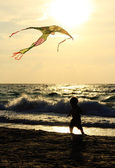 Kid playing with kite on the sea — Stock Photo
