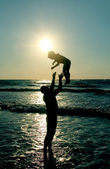 Father and son on the sea at sunset — Stock Photo