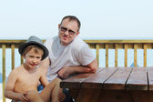 Happy father and his son sitting on summer cafe on the beach — Stock Photo
