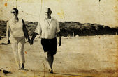Happy senior couple walking together on a beach. Photo in old im — Photo