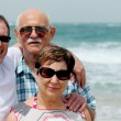 Adult son with his parents  walking on the beach — Stock Photo