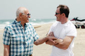 Adult son and father walking together on the beach — Stock Photo