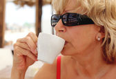 Portrait ofattractive woman with cup of hot drink (coffee or tea) at the beach — Foto Stock