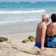 Portrait of happy senior couple sitting together on a beach — Stock Photo