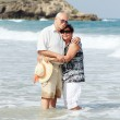 Happy senior couple walking together on a beach — Stock Photo