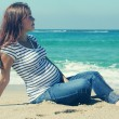 Beautiful pregnant woman sitting on the beach — Stock Photo