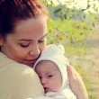 Young mother with her newborn baby outdoor — Stock Photo