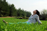 Mature woman sitting in grass — Photo