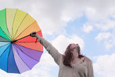 Woman with umbrella on the background of cloudly sky — Stock Photo