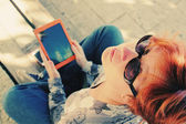 Redhead woman with tablet outdoors — Stockfoto