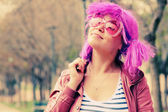 Beautiful young woman with pink sunglasses and purple hair — Stockfoto