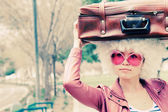 Beautiful young woman with vintage bag standing in the city park — 图库照片
