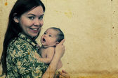 Young mother with her baby. Photo in old image style — 图库照片