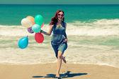 Mladá zrzka žena drží barevné balónky — Stock fotografie