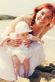 Portrait of happy loving mother and her baby at the beach — Stock Photo