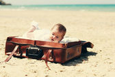 Cute 2-month old baby lying in vintage case on the beach — Stock Photo
