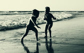 Two happy kids playing on the beach — Stok fotoğraf
