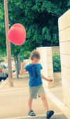 Cute 6 years old boy holding red balloon — Stock Photo