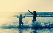 Two happy kids playing on the beach at sunset — Stock Photo