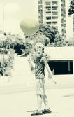 Cute 6 years old boy holding red balloon — Stok fotoğraf