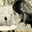 Girl looks at herself in the glass jar. Photo in old image style — Stock Photo #9832356
