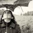 Girl with umbrella in the field. Photo in old color image style. — Stock Photo #9835348