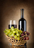 Wine and grapes in basket — Stock Photo