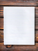 Lined paper on dark table — Stock Photo