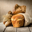 Bread in assortment and wheat - Stock Photo