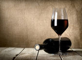 Botella negra y vino tinto — Foto de Stock