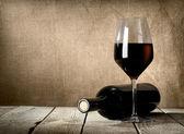 Zwarte fles en rode wijn — Stockfoto