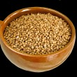 Buckwheat in ceramic bowl  on black — Stock Photo