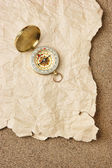 Compass on old sheet paper against the background of sand — Stock Photo