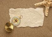 Kompass auf dem alten blatt papier vor dem hintergrund der sand — Stockfoto